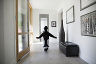 Boy in killer whale costume walking through foyer with arms outstretched - HEROF13246