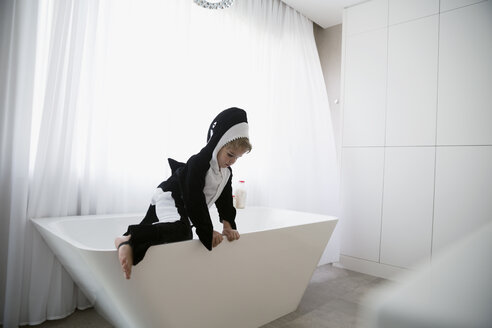 Boy in killer whale costume climbing out of bathtub - HEROF13252