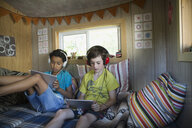 Boys with headphones using digital tablets in treehouse - HEROF13273