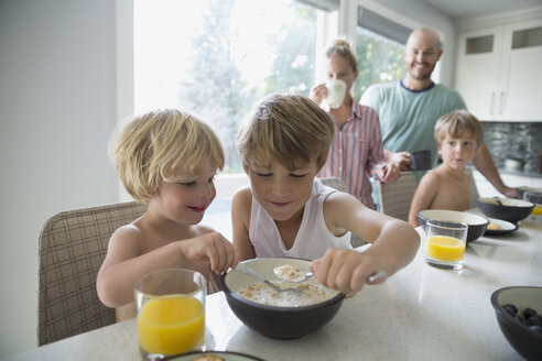 Boys sharing cereal at breakfast in kitchen - HEROF13297