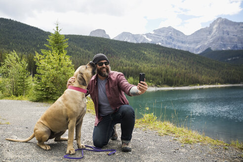 Bearded man with dog taking selfie with camera phone at remote mountain lakeside - HEROF13306