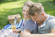 Blonde couple laughing drinking champagne on picnic blanket in park - HEROF13318