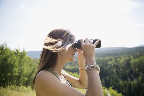 Brunette woman looking at sunny view with binoculars - HEROF13321