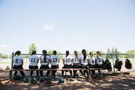 Middle school girl softball team sitting on bench - HEROF13324