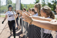 Middle school girl softball team high fiving teammate over fence - HEROF13327