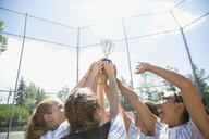 Middle school girl softball team holding trophy and cheering - HEROF13330