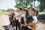 Middle school girl softball team standing in a row watching game - HEROF13336
