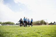 Middle school girl soccer team walking onto sunny field - HEROF13351
