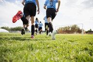 Middle school girl soccer team running onto sunny field - HEROF13354