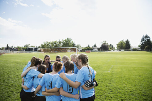 Middle school girl soccer team huddling on field - HEROF13357
