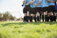 Middle school girl soccer team huddling on field - HEROF13360
