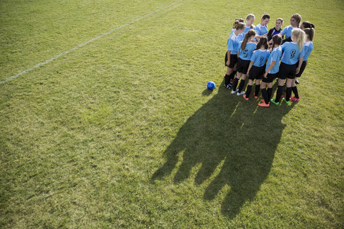 Middle school girl soccer team huddling with coach on sunny field - HEROF13363