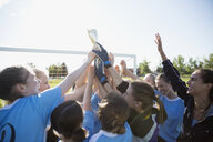 Middle school girl soccer team celebrating and cheering with trophy - HEROF13366