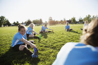 Middle school girl soccer team stretching at practice on sunny field - HEROF13372