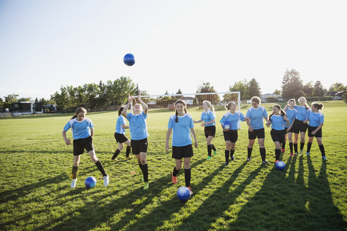 Middle school girl soccer team practicing on sunny field - HEROF13375