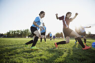 Middle school girl soccer players playing game on field - HEROF13381