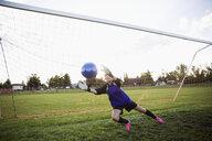 Middle school girl soccer goalie catching soccer ball at net - HEROF13384
