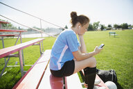 Middle school girl soccer player listening to music with headphones and mp3 player on bleachers - HEROF13390