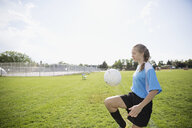 Middle school girl soccer player bouncing ball on knee on sunny field - HEROF13393