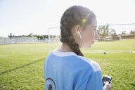 Middle school girl soccer player listening to music with headphones and mp3 player on sunny field - HEROF13396