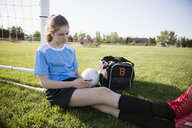 Middle school girl soccer player listening to music with headphones and mp3 player at goal net post on sunny field - HEROF13402