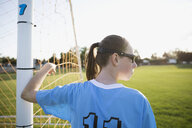 Middle school girl soccer player leaning on goal net post looking away - HEROF13405