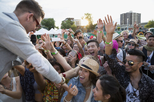Musician reaching for crowd at summer music festival - HEROF13414