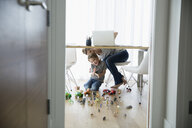 Mother at laptop peeking under table at son playing with toys - HEROF13429