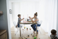 Mother and son playing with connector sticks at dining table - HEROF13432
