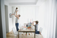 Mother holding baby overhead next to son playing with connector sticks in dining room - HEROF13435