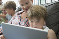 Mother and son using digital tablet on living room sofa - HEROF13447