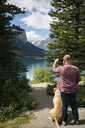 Man with dog photographing remote mountain and lake with camera phone - HEROF13450