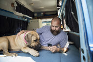 Man with dog relaxing and texting with cell phone in camper van - HEROF13453