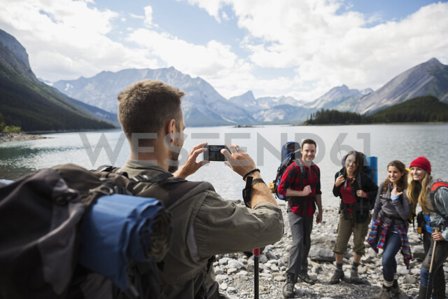 Man with camera phone photographing friends hiking at remote mountain lakeside - HEROF13456 - Hero Images/Westend61