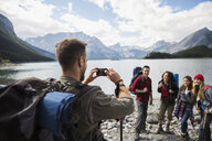 Man with camera phone photographing friends hiking at remote mountain lakeside - HEROF13456