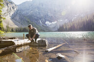 Man washing hands in sunny remote mountain lake - HEROF13459