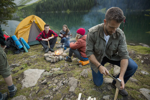 Man splitting wood with ax near campfire at lakeside campsite - HEROF13462