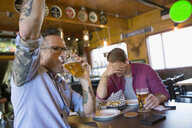 Men friends drinking beer and cheering watching game at bar - HEROF13477