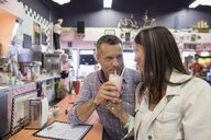 Mature couple sharing milkshake at soda fountain shop - HEROF13480