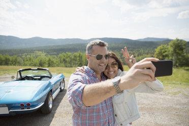 Mature couple taking selfie near convertible at rural overlook - HEROF13486
