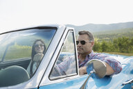 Mature couple riding in convertible - HEROF13489
