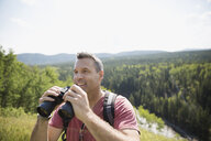 Mature man using binoculars looking at sunny view - HEROF13492