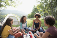 Mother and daughters playing cards at rural campsite - HEROF13495