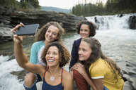 Mother and daughters taking selfie with camera phone at waterfall - HEROF13501