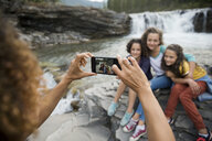 Mother photographing daughters with camera phone at waterfall - HEROF13504