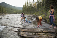 Mother and daughters skipping stones at creek - HEROF13513