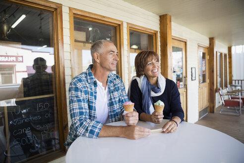 Mature couple eating ice cream cones outside ice cream shop - HEROF13516