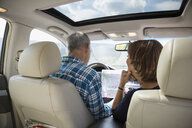 Mature couple looking at map inside car - HEROF13522