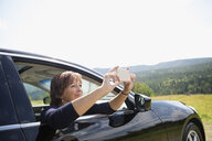 Mature woman photographing sunny rural view from car window - HEROF13525