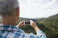Mature man photographing treetops with camera phone - HEROF13534